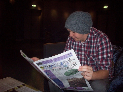Enjoying th' paper with a pint